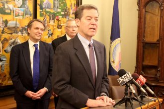 Governor Sam Brownback speaking in 2017 as Lieutenant Governor Jeff Colyer looks on. (Photo by Stephen Koranda)