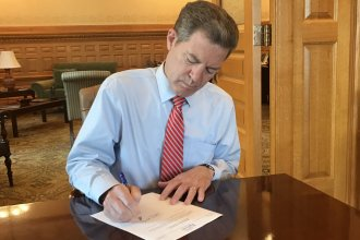Governor Brownback signing the veto message. (Photo from the governor's office)