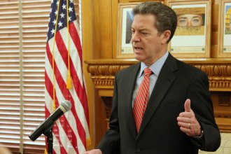 Governor Brownback speaking to reporters at the Statehouse. (Photo by Stephen Koranda)