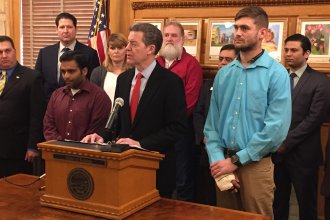 Governor Sam Brownback and the survivors of the shooting. To the left is Alok Madasani and to the right is Ian Grillot. (Photo by Stephen Koranda)
