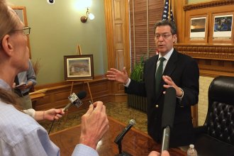 Governor Brownback speaking to reporters earlier this year. (Photo by Stephen Koranda)