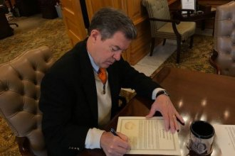 Governor Brownback signs the pardon. (Photo from the governor's office)