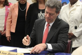 Governor Brownback signs the welfare bill into law. (Photo by Stephen Koranda)