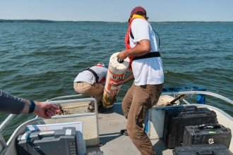 Researchers pull a buoy from Clinton Lake to remove data from sensors attached to it. (Photo by Brian Grimmett, Kansas News Service)