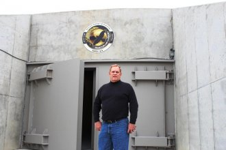 Survival shelter developer Larry Hall stands outside the blast doors of his luxury bunker near Concordia, Kansas.  The former Atlas missile silo has been converted into high-end apartments that sell for millions.  Hall says this shelter is sold out.  (Photo by Frank Morris)