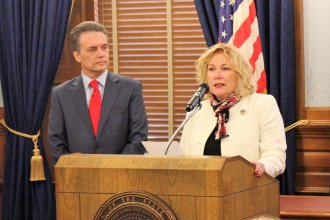 Gina Meier-Hummel, right, is Lt. Gov. Jeff Colyer's pick to serve as secretary of the Kansas Department for Children and Families. Colyer, left, announced her appointment Wednesday in Topeka. (photo credit: Stephen Koranda)