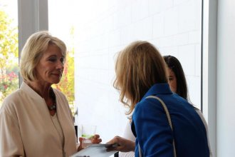 State Representative Cindy Holscher, right, an Olathe Democrat, hands DeVos a packet of statements from groups that oppose her position on school choice. (Photo: Kansas News Service)