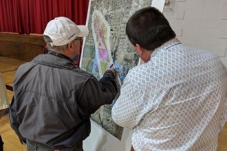 KDHE employee Kevin Moon, right, helps a Haysville resident locate his house on a map during a public meeting in December. (Photo Credit: Brian Grimmett, KMUW Radio)