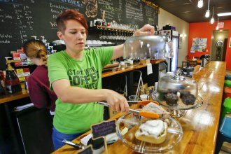 "Mandy Fincham and her husband run the Kettle in Beloit, Kansas. Some people think ""quality-of-life"" initiatives like their cafe and wine bar can make a difference between small towns shrinking smartly or withering on the vine. (Photo by Chris Neal / Kansas News Service)"