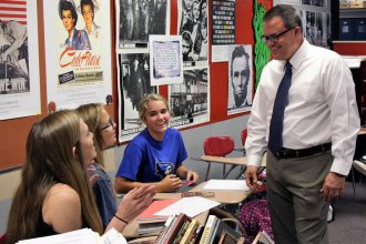 Nathan McAlister, right, recently moved from rural Royal Valley Middle School to Seaman High School in part for a salary increase. From left are Seaman students Chloe Carter, Riley Polter and Sophie Sparks. (Photo by Celia Llopis-Jepsen / Kansas News Service)