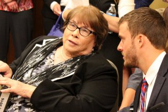 Secretary Gilmore speaking to one of her staff members before the hearing. (Photo by Stephen Koranda)