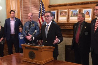 Governor Sam Brownback at the signing ceremony in his office. (Photo by Stephen Koranda)