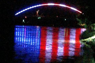 Old Glory, reflected by the Missouri River as it flows under the Amelia Earhart Memorial Bridge in Atchison.  (Photo by J. Schafer)