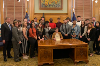 """JAG-K Day at the Kansas Statehouse, February 2020.  JAG-K students pose for a photo with Kansas Governor Laura Kelly, a supporter of JAG-K.  JAG or, """"Jobs for America's Graduates,"""" is a national program designed to help students suceed in life.  The Kansas Chapter is called JAG-K. (Photo from JAG-K)"""