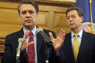 Lt. Governor Jeff Colyer (left) speaks with reporters as Governor Sam Brownback (right) looks on.  (Photo by Stephen Koranda)