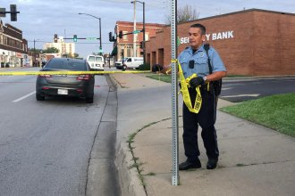 A Kansas City, Kansas, police officer puts up tape near the intersection of 10th and Central, where a bar shooting happened overnight.  (Photo by Elle Moxley / KCUR)