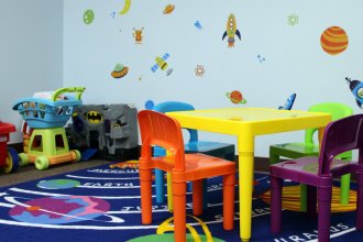 A kid-friendly room in KVC's Topeka office is decorated with a space theme. The contractor is used to having kids hanging out in kid-friendly spaces of its offices, but is still adjusting to a growing number of children spending nights there. (Photo by Madeline Fox / Kansas News Service)
