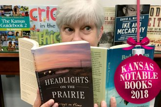 Kaye McIntyre surrounded by Kansas Notable books