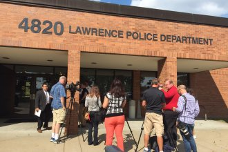 Reporters wait outside the Investigations and Training Center of the Lawrence Police Department for an update on the investigation into the fatal weekend shooting. (Photo by J. Schafer)