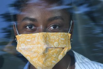 A woman wears a cloth mask, as recommended by the CDC and World Health Organization to slow the spread of COVID-19. (Photo illustration by Carlos Moreno, KCUR)