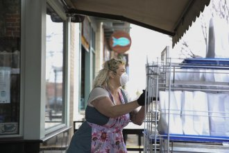 Meg Heriford puts free bagged lunches outside of the Ladybird Diner in downtown Lawrence. Her restaurant has been closed since March 15, but Heriford and staff are preparing meals for those who need them. (Photo by Nomin Ujiyediin, Kansas News Service)