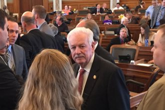House Speaker Ray Merrick talks with staff members after debate on the bill was blocked. (Photo by Stephen Koranda)