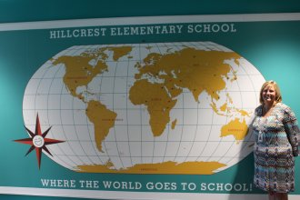 Hillcrest Elementary School Principal Tammy Becker stands next to a map near the entrance to the school.  Hillcrest has a number of immigrant students who come from all over the world, as indicated by markers on the map.  (Photo by J. Schafer)