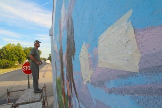 Hays artist Matt Miller stands on a scaffold as he puts the finishing touches on the town's latest mural. (Photo by David Condos, Kansas News Service)