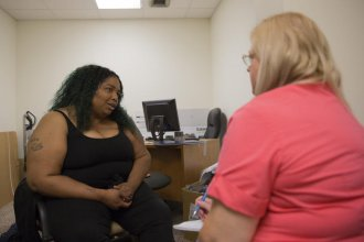 Peer support specialist Sheri Hall (left) gives advice to Susan Haynes. Hall doesn't have a degree in social work or psychology, but she and Haynes bond over their Christian faith, love of writing and shared history of anxiety.  (Photo by Nomin Ujiyediin / Kansas News Service)