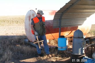 Rex Buchanan, with the Kansas Geological Survey, measuring groundwater levels during a trip out to western Kansas in 2006.  (Photo by Brownie Wilson, KGS)