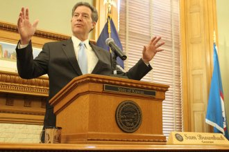Kansas Governor Sam Brownback discussed his signature tax policy and other key issues during his years as governor during a news conference Thursday at the Statehouse. (Photo by Susie Fagan, Kansas News Service)