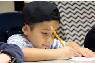 A first-grader practices spelling at Broken Arrow Elementary in Lawrence during a small-group phonics lesson in 2018. (Photo by Celia Llopis-Jepsen, Kansas News Service)