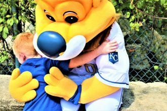 A child hugs Sluggerrr after having his picture taken with the mascot during a recent game at Kauffman Stadium (Photo by Jim Mclean, Kansas News Service)