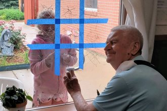 Bob Corbin, a resident at Bethany Home, plays tic-tac-toe through a window with Sydney, the daughter of a staff member. (Photo courtesy of Jennifer Cantrell)