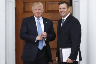 Kris Kobach was photographed carrying a stack of papers with headings indicating they were related to voter fraud and immigration policy. (Associated Press file photo)