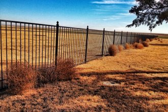 Tumbleweeds, piling up on the prairie.  This cemetery fence in Ford County has captured several of the rolling weeds. (Photo by Cheryl Unruh)