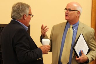 Democratic Rep. Jim Ward (right) speaks to Republican Rep. John Barker before the meeting. (Photo by Stephen Koranda)