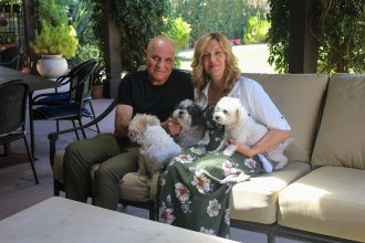 Tom and Dana Saputo sit in their backyard with their three dogs. Tom Saputo's double-lung transplant was fully covered by insurance, but he was responsible for an $11,524.79 portion of the charge for an air ambulance ride.