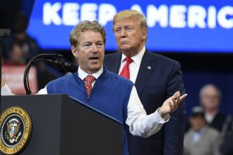 President Trump listens Monday as Sen. Rand Paul, R-Ky., speaks during a campaign rally in Lexington, Ky., in which Paul called on the media to release the name of the whistleblower.