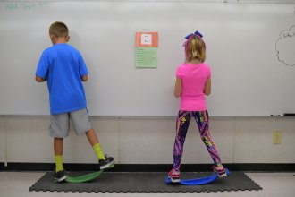 "Two fourth-graders rock side to side while doing math equations at Charles Pinckney Elementary School's ""Brain Room"" in Charleston, S.C., in 2015."