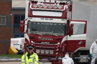 Essex authorities examine the truck that was found to contain 39 dead migrants. Police said Thursday the victims have been identified as Vietnamese nationals.