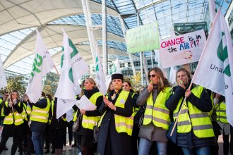 "Flight picketing in front of the Munich Airport Thursday, some holding signs with slogans that read ""Change is in the air???"" Lufthansa has cancelled a total of 1300 flights due to the announced 48-hour strike by flight attendants."