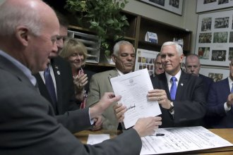 Vice President Mike Pence files for President Donald Trump to be listed on the New Hampshire primary ballot to New Hampshire Secretary of State Bill Gardner, left, Thursday, Nov. 7, 2019, in Concord, N.H.