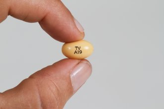 A progesterone pill held between a woman's fingers.