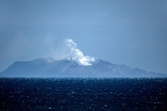 Steam rises from the volcano on New Zealand's White Island on Tuesday, one day after an eruption there left at least six people dead, more than 30 injured and still others missing. Questions linger about why so many people were allowed so close to the active volcano.