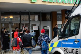 Police officers guard the doors of a teaching hospital in Ostrava, Czech Republic, after a gunman carried out a mass shooting in its waiting room Tuesday morning.
