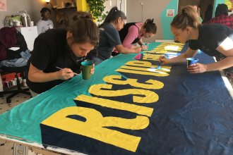 Volunteers paint a banner for the front of the demonstration. Organizers hosted the event to bring supporters together ahead of this year's Women's March, scheduled for Saturday.