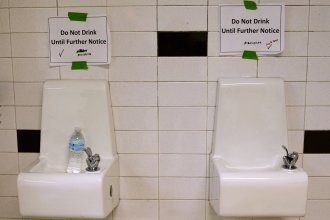 """Drinking fountains are marked """"Do Not Drink Until Further Notice"""" at Flint Northwestern High School in Flint, Mich., in May 2016. After 18 months of insisting that water drawn from the Flint River was safe to drink, officials admitted it was not."""