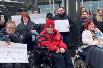 Members of the Illinois Network of Centers for Independent Living (INCIL) demonstrate in front of the Bloomington-Normal Amtrak station in Illinois to demand the suspension of an Amtrak policy that led to exorbitant fees for removing train seats to accommodate riders in wheelchairs. Later on Wednesday, Amtrak announced it would suspend the policy.