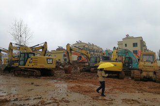 A man holding an umbrella walks past excavators at the construction site where a new quarantine and treatment center is being built to treat patients of a new coronavirus.